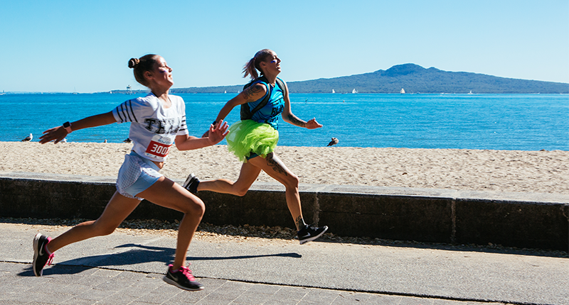 Two women running on Auckland's waterfront with Rangitoto in the background