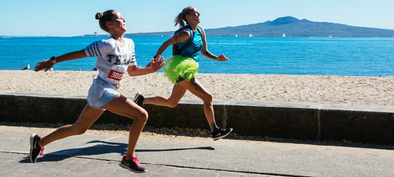 Two women running on the waterfront with Rangitoto Island in the background.