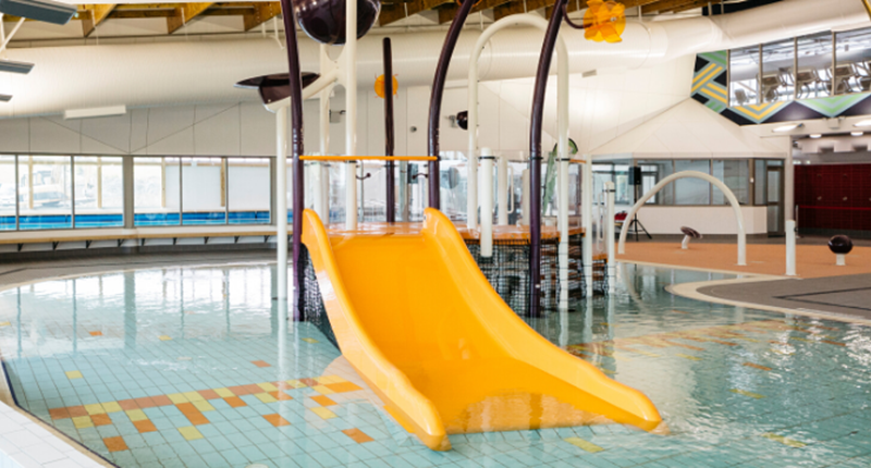 Bright yellow plastic water slide feature at the Albany Stadium Pools