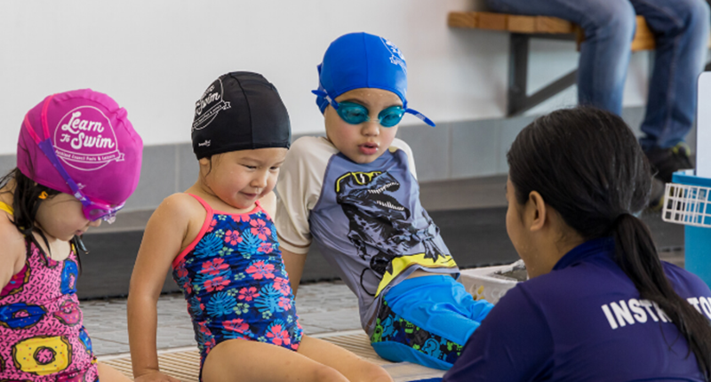 a learn to swim instructor with 3 children in togs and caps learning to swim