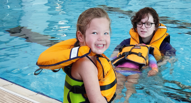 a young girl in a life jacket sitting on the side of the pool and an instructor and second girl in the water floating