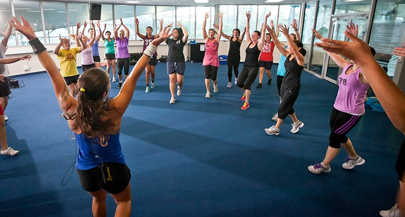 A mixed age group fit class of women wave their hands in the air.