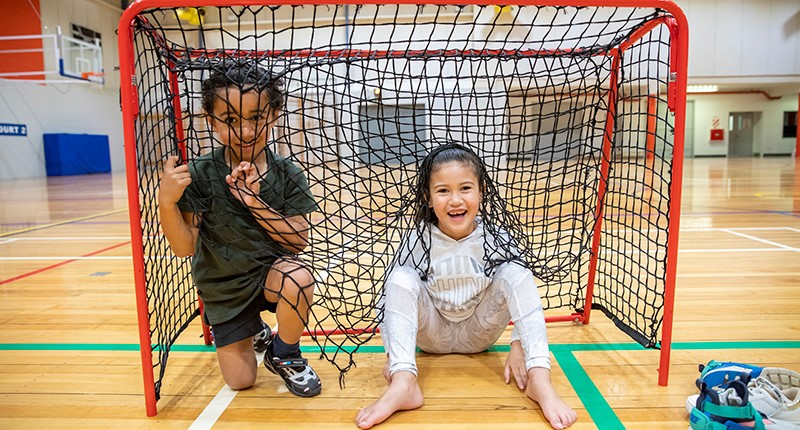 a young boy and girl sitting in a soccer goal