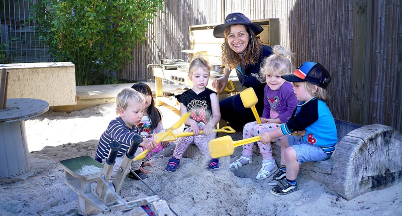Kauri Kids teacher with 5 children in sandpit with spades