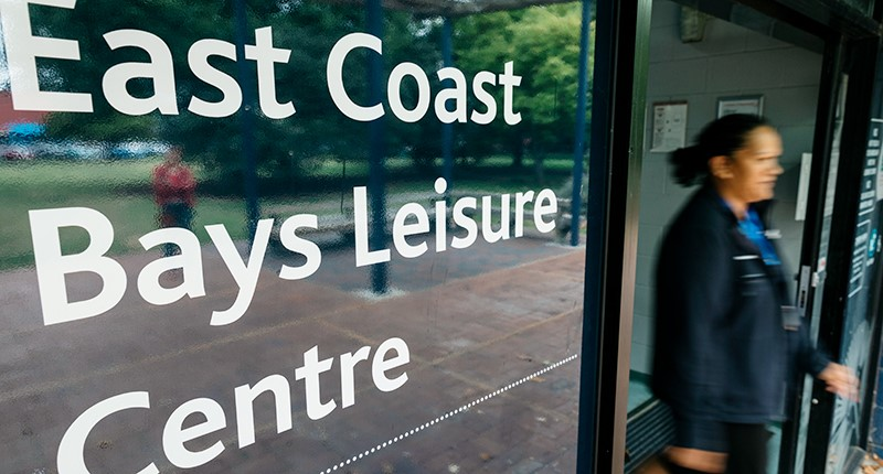 Closeup shot of East Coast Bays Leisure Centre main sliding door entrance with a female staff member shown exiting through the doors.
