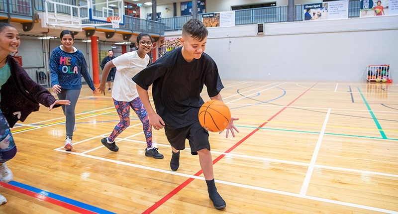 A team of young people chase a player dribbling a basketball inside the stadium at the Allan Brewster Leisure Centre.
