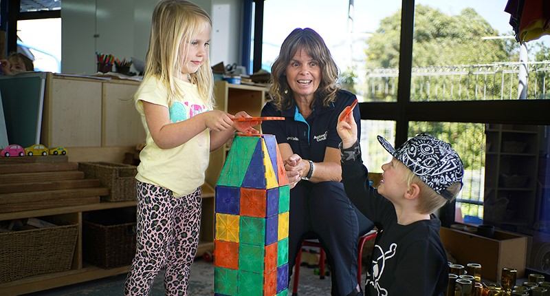 A caregiver wearing a council uniform supervises while two children play with colourful building blocks.