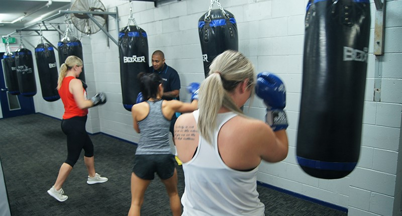 three ladies in fitness boxing session with instructor