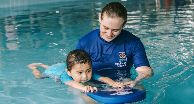 A female Learn to Swim instructor holds a kickboard while she teaches a young child how to swim in the pool
