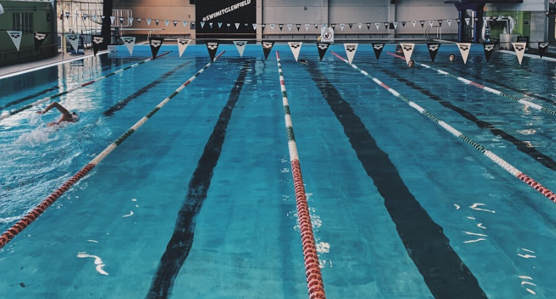a photo of the glenfield pool with lane ropes and a lone swimmer