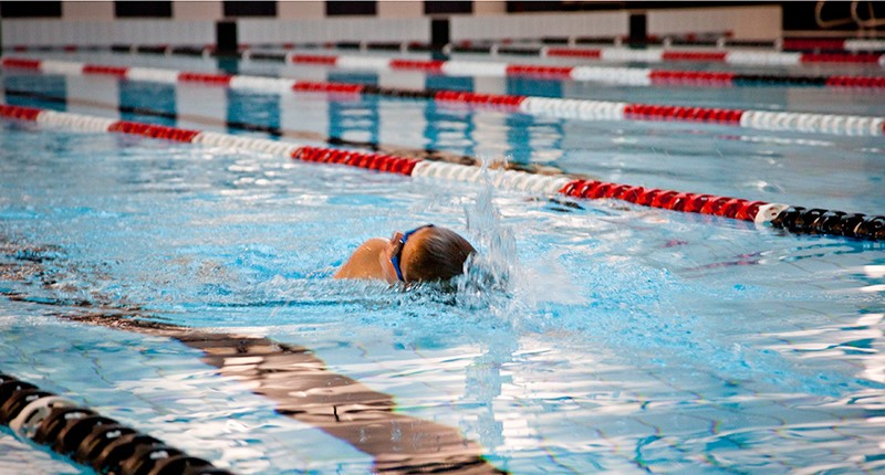 young boy taking a breath while swimming a length