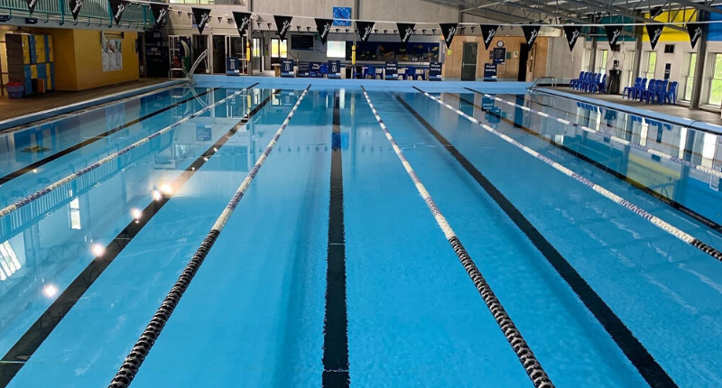 photo of pool with lane ropes and flags over the water