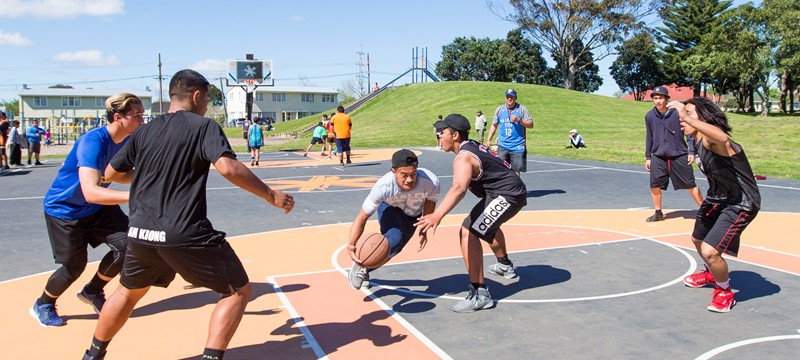 A group of males play basketball on a sunny outdoor court.