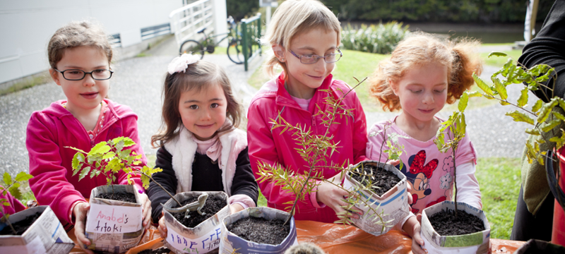 A group of young girls plant seedlings during a school holiday programme.